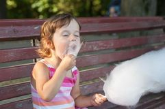 Llittle girl eating cotton candy in the park Royalty Free Stock Photos
