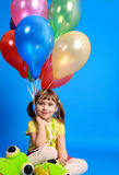 Llittle girl holding colorful balloons Stock Images