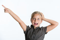 Llittle girl pointing her finger up on a white background. Royalty Free Stock Photo