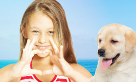 Llittle girl showing heart hands and labrador puppy Royalty Free Stock Image