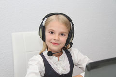 Llittle girl sits in front of a laptop with headphones and learn Royalty Free Stock Photo