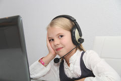 Llittle girl sits in front of a laptop with headphones and learn Stock Photo