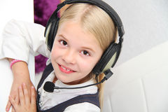 Llittle girl sits in front of a laptop with headphones and learn. Photo of the Llittle girl sits in front of a laptop with headphones and learn Royalty Free Stock Image