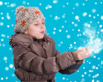 Llittle girl in winter clothes blowing snow Stock Photo