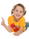 Llittle girl in a yellow shirt holds her thumb up Stock Image
