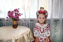 llittle Mädchen im ukrainischen nationalen Kostüm mit Kranz auf ihrem Kopf sitzt nahe der Tabelle lizenzfreies stockbild