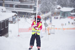 Llittle skiing girl holding tight a handle of a ski tow Royalty Free Stock Photos