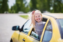 Llittle smiling girl is sticking her head out the car window and Royalty Free Stock Image