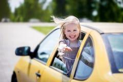 Llittle uśmiechnięta dziewczyna jest wtykać jej przewodzi out fotografia stock
