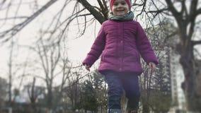 Llittlemeisje die langs verschansing in stadspark lopen en rond en bij camera kijken glimlachen Kinderachtige uitdrukkingen kinde stock videobeelden