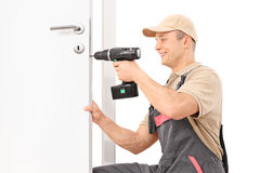 Llocksmith screwing a screw on lock of a door. Young male locksmith screwing a screw on a lock of a door with a hand drill isolated on white background Stock Photo