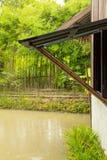 Llover la ventana abierta, usando los polos de bambú al apoyo fluye en el p imagenes de archivo