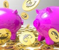 Llover monedas en beneficios de la demostración de Piggybanks Fotos de archivo libres de regalías
