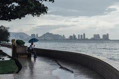 Lloviendo en el parque que cerca de la costa con un hombre que lleva a cabo el paraguas y ver paisaje marino y el paisaje urbano  Imagenes de archivo