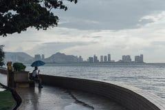 Lloviendo en el parque que cerca de la costa con un hombre que lleva a cabo el paraguas y ver paisaje marino y el paisaje urbano  Fotos de archivo libres de regalías