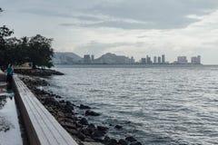 Lloviendo en parque, cerca de la costa con paisaje marino y el paisaje urbano de George Town, Penang, Malasia Imagenes de archivo