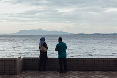 Lloviendo en parque, el hombre y la mujer están viendo paisaje marino y paisaje urbano de la costa de George Town, Penang, Malasi Foto de archivo