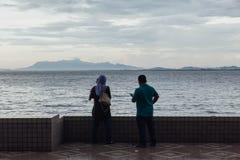 Lloviendo en parque, el hombre y la mujer están viendo paisaje marino y paisaje urbano de la costa de George Town, Penang, Malasi Fotografía de archivo