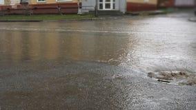 Llueva caer en el camino, atravesando el dren de la alcantarilla Impulsión de los coches en una manera inundada almacen de video