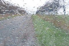 Llueva el descenso en ventana delantera del coche, opinión del camino a través de la ventana foto de archivo libre de regalías