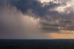 Llueva la colada abajo de las nubes en una distancia Foto de archivo