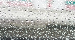 Llueva los descensos en la pantalla de la ventana con los fondos borrosos Foto de archivo libre de regalías