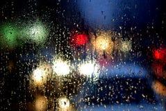 Llueva los descensos en ventana y fondo borroso de los semáforos Foto de archivo libre de regalías