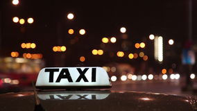 Lluminated taxi sign on top of a cab in a city street stock footage