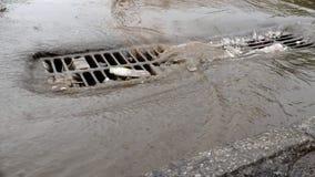 Lluvia de Havy en una ciudad, una calle inundada y una cubierta de boca del dren de la tormenta metrajes