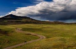 Lluvia de la tormenta de las colinas de la carretera con curvas soleada Imagenes de archivo