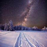 Lluvia de meteoritos fantástica del invierno y las montañas coronadas de nieve foto de archivo libre de regalías