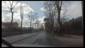 Lluvia en tiempo real que cae en el parabrisas, con el coche corre a lo largo del camino
