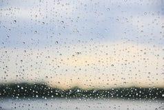 Lluvia en una ventana con la línea de la orilla en el fondo y el cielo azul Foto de archivo