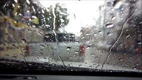 Lluvia que cae a través del parabrisas con el sonido metrajes