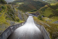 Llyn Brianne Reservoir. The overflow at Llyn Brianne Reservoir in Wales in a dramatic landscape format Royalty Free Stock Photos