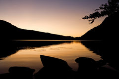 Llyn Ogwen. A romantic sunrise with silhouete of boulders and mountains surrounting Llyn Ogwen in Snowdonia, Wales Stock Photo
