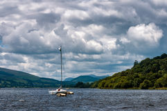 Llyn Tegid. Boat on Llyn Tegid, Bala, Wales, with dramatic clouds in the sky. Summer storm coming Royalty Free Stock Photography