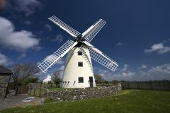 Llynnon Mill. A working windmill with two wattle and daub roundhouses Royalty Free Stock Images