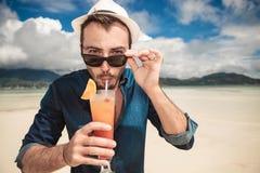 Lman on the beach drinking a orange cocktail Stock Photo