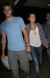 LMiley Cyrus y novio Liam Hemsworth en LAX imagenes de archivo