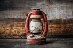 Lâmpada antiquado da lanterna do óleo do querosene do vintage que queima-se com uma luz macia do fulgor com o assoalho de madeira Imagem de Stock