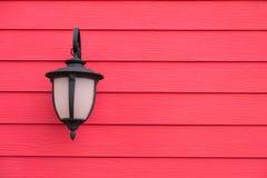 Lâmpada de parede antiga do vintage na parede de madeira vermelha, para o fundo com Fotografia de Stock Royalty Free