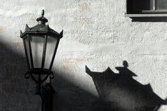 Lámpara de calle con la sombra en la pared Imagen de archivo