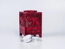 Lámpara roja del aroma con las velas en el fondo blanco Imagenes de archivo