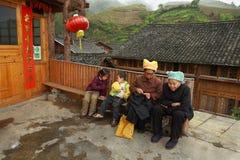 Ländliches China, asiatische Großmutter mit Enkelkindern, sitzen auf Bank. Stockbilder