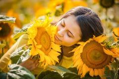 Ländliches Mädchen in den Feldsonnenblumen Lizenzfreies Stockfoto