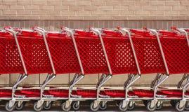 Línea de carros de compras rojos por la pared de ladrillo Imagenes de archivo