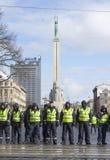 Línea de policía en el monumento delantero de la libertad en Riga, Letonia Foto de archivo libre de regalías