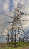 Líneas eléctricas eléctricas contra el cielo en la salida del sol Foto de archivo