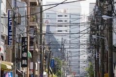Líneas eléctricas que entrecruzan sobre la calle de la ciudad Fotos de archivo